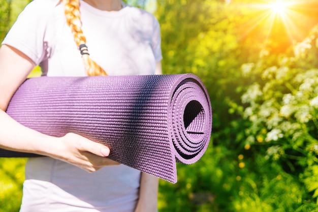 Sportiva che va alla pratica dello yoga con tappetino pronto per l'esercizio in palestra ragazza sportiva che tiene tappetino yoga e bottiglia d'acqua prima del concetto di allenamento fitness di sport stile di vita attivo e salute