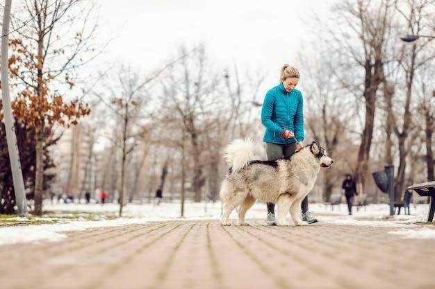 Sportiva in un parco con il suo cane il giorno di inverno nevoso. fitness invernale, freddo, neve, cani, animali domestici, persona con cani