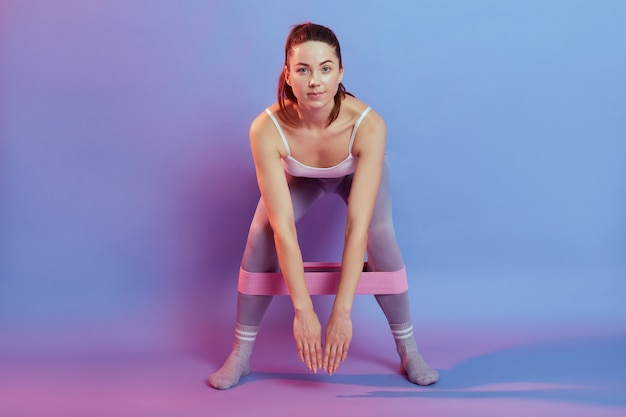 La sportiva esegue esercizi con fascia di resistenza, piegandosi in avanti