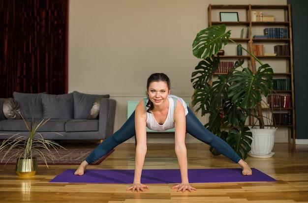 Sportiva esegue esercizi fisici sulla stuoia in una stanza a casa
