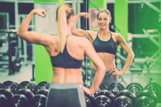 La sportiva posa davanti allo specchio in palestra