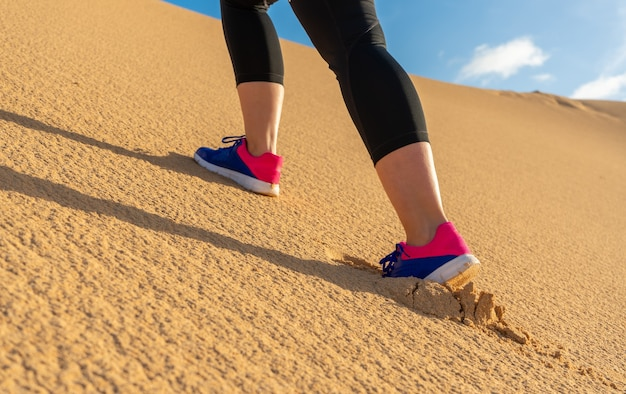 Sportiva in esecuzione tra le dune - messa a fuoco selettiva