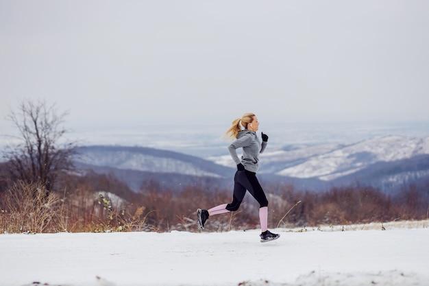 Sportiva che corre veloce in natura sul sentiero innevato in inverno. stile di vita sano, fitness invernale, freddo
