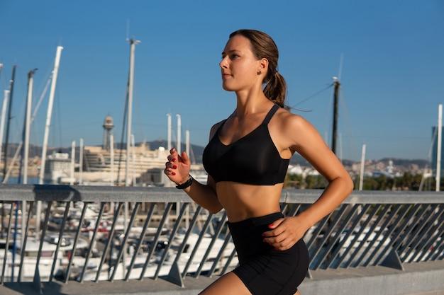 Sportiva che corre vicino al porto in città