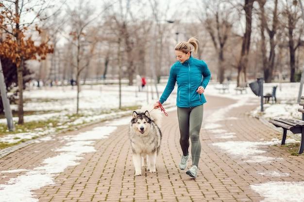 Sportiva in esecuzione con il suo cane in un parco in una fredda giornata invernale. animali domestici, fitness invernale, corridore, stare insieme