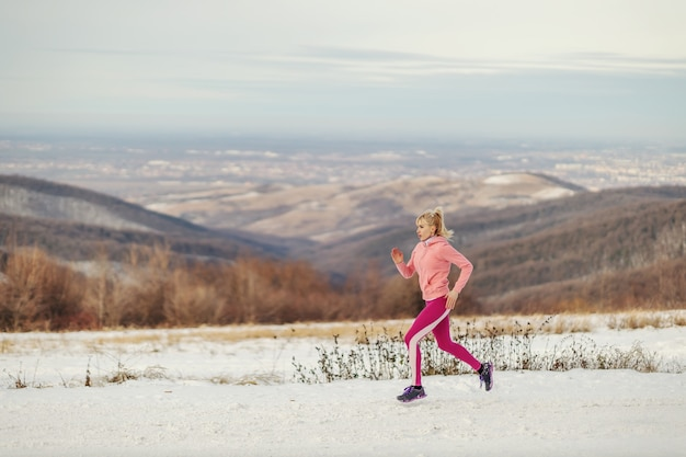 Sportiva in forma in esecuzione in natura al giorno d'inverno nevoso. abitudini salutari, fitness invernale, esercizi cardio