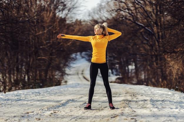 Sportiva in forma in piedi sul sentiero innevato in natura e facendo esercizi di riscaldamento alla soleggiata giornata invernale.