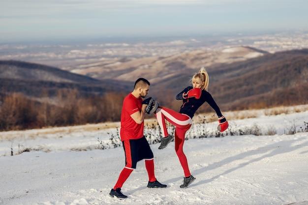 Sparring sportiva con guantoni da boxe in natura al giorno di inverno nevoso con il suo allenatore.