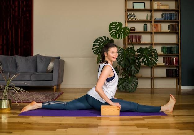 Una sportiva in uniforme sportiva esegue le spaccate con l'aiuto di mattoni sul tappetino nella stanza