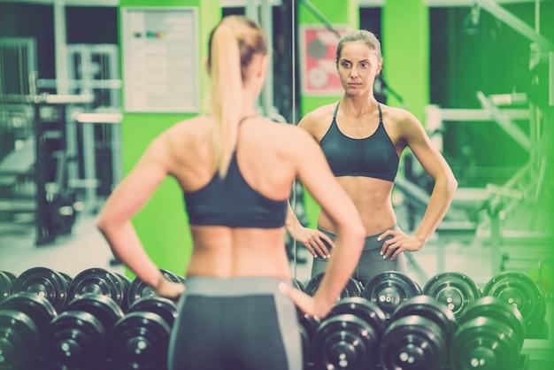 La sportiva in piedi davanti allo specchio in palestra