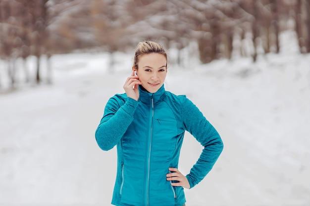Sportiva in piedi in natura il giorno di inverno nevoso con la mano sull'anca e mettendo gli auricolari.