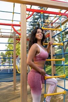 Sportiva in abiti stretti fitness in posa sul campo sportivo tenendo le scale