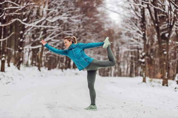 Sportiva in abito caldo facendo esercizi di yoga nella foresta innevata.