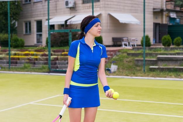 Sportiva che indossa un abbigliamento sportivo in possesso di palline da tennis e una racchetta durante una partita su un campo all'aperto in estate o in primavera
