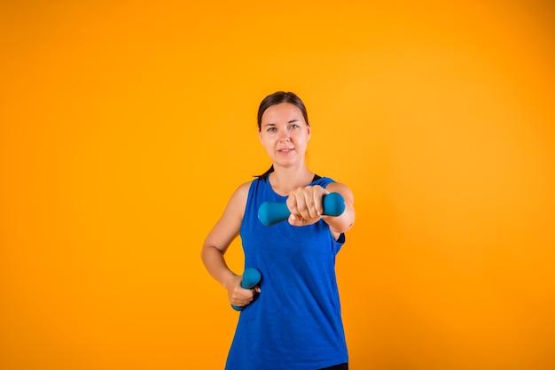 Sportiva con manubri su una parete arancione con spazio per il testo