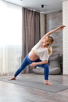 Bella donna bionda incinta sportiva che fa esercizio di affondo in piedi nella postura di angolo laterale esteso a casa