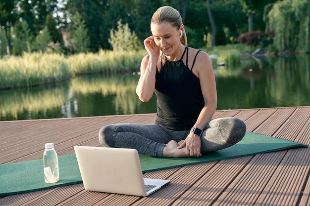 Bella donna sportiva che sembra allegra guardando un tutorial su un laptop mentre fa yoga su un tappetino in