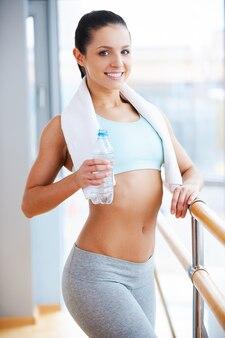 Bellezza sportiva. attraente giovane donna in abbigliamento sportivo che tiene in mano una bottiglia d'acqua e sorride mentre si trova in un centro benessere