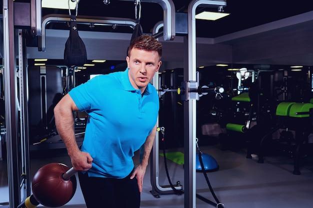 Un uomo biondo sportivo facendo esercizi con la palla in palestra