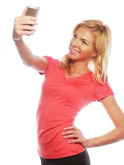 Donna bionda sportiva che fa selfie, colpo dello studio