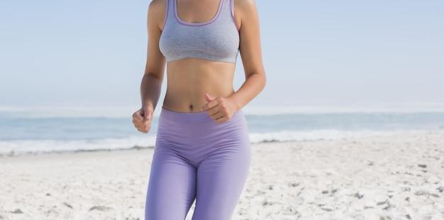 Bionda sportiva sulla spiaggia a fare jogging