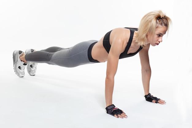 Femmina bionda sportiva che fa esercizio della plancia del gomito isolato