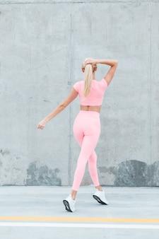 Modello di fitness donna bionda sportiva con bel corpo sexy in abbigliamento sportivo rosa moda con scarpe bianche cammina per strada, vista posteriore