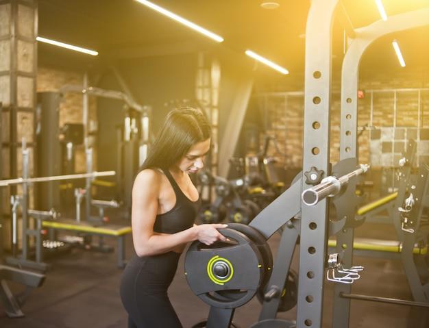 Donna castana sportiva che mette il disco del peso per il bilanciere contro il fondo della palestra