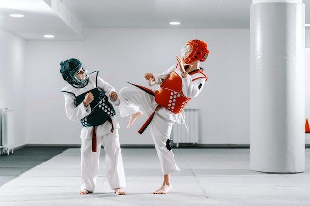 Ragazzi caucasici sportivi che hanno addestramento di taekwondo in palestra bianca. un ragazzo che prende a calci l'altro.