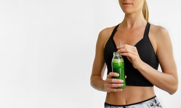 Donna caucasica sportiva che tiene la bottiglia verde del frullato. concetto di stile di vita sano.