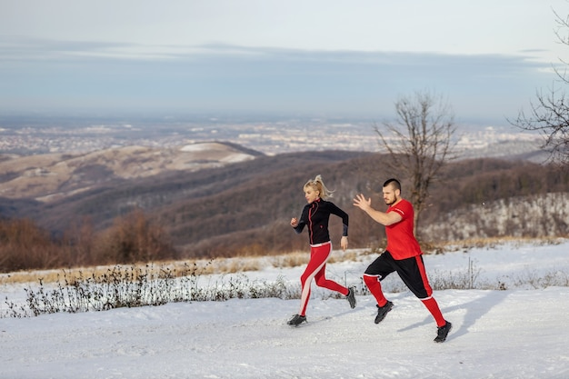 Coppia sportiva da corsa in natura al giorno di inverno nevoso.