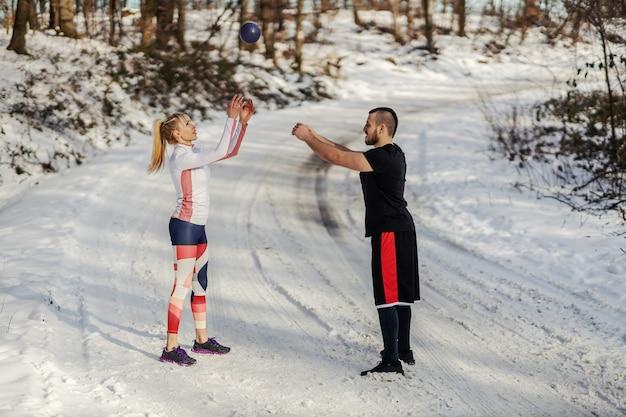 Coppia sportiva in piedi nella neve in natura e facendo esercizi di riscaldamento con palla fitness in inverno.