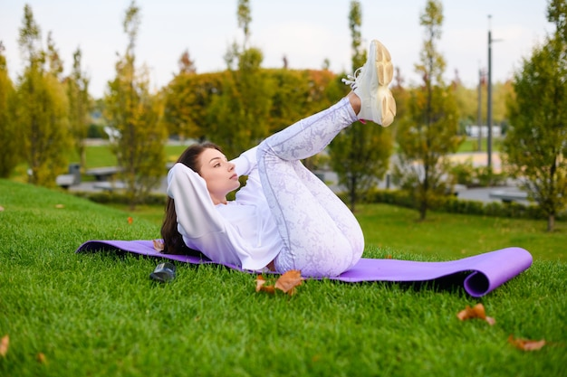 La donna sportiva in abiti bianchi giace sul tappeto all'aperto e fa stretching, fitness, addominali sullo sfondo della natura