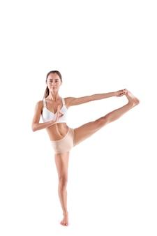 Bella donna in forma sportiva in abiti sportivi che fa yoga isolato su fondo bianco. esercizio di controllo dell'equilibrio, lunghezza intera in studio.