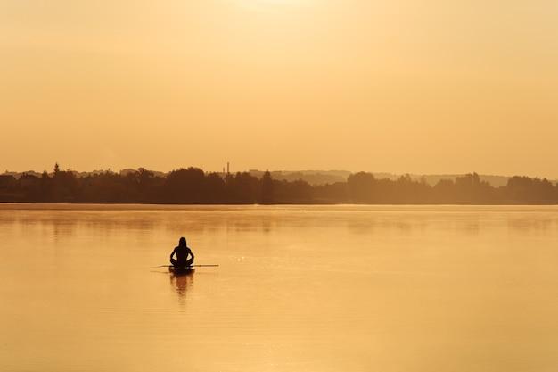 Ragazzo sportivo in forma seduto con le gambe incrociate sul paddle board nel mezzo del lago nebbioso.