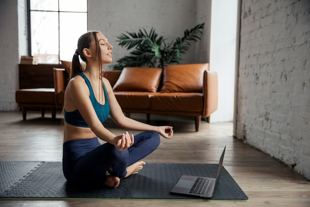 L'allenatore sportivo della donna snella pratica il video di formazione online dell'istruttore di hatha yoga al laptop, medita la postura di sukhasana, rilassati e respira.