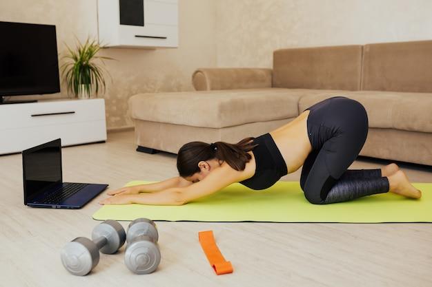 La donna snella in forma sportiva pratica la formazione online video con l'istruttore di yoga medita, rilassati e respira il concetto di stile di vita sano.