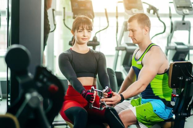 Ragazza sportiva che fa esercizi di peso con l'assistenza del suo personal trainer