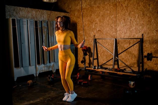 Una ragazza sportiva salta su una corda in una moderna palestra foto in movimento