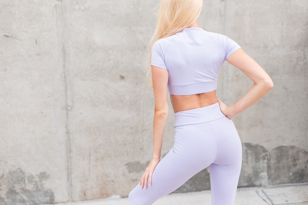 Modello sportivo da ragazza con corpo fitness in abbigliamento sportivo viola alla moda per strada