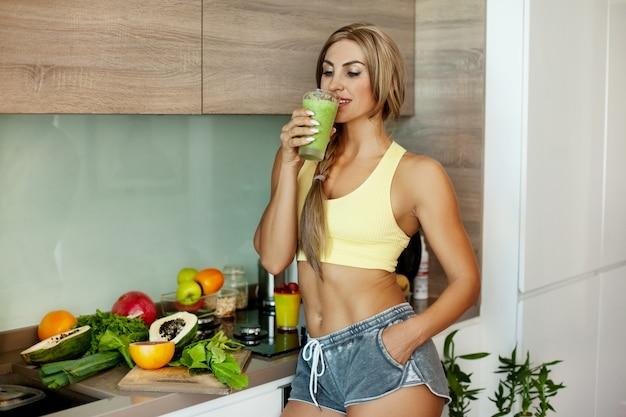 Una ragazza sportiva sta in cucina e beve un frullato verde detox per colazione, accanto a frutta e verdura fresca. il concetto di una sana alimentazione. salute, sport, fitness-nutrizione.