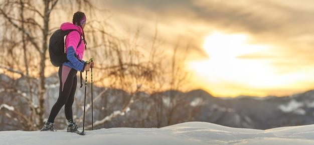 Una ragazza sportiva guarda il tramonto durante un'escursione con le ciaspole