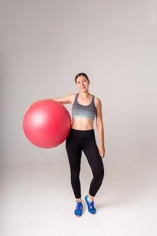 Ragazza sportiva con una palla fitness integrale su un bianco
