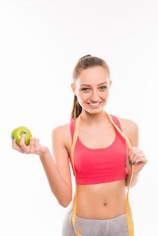 Ragazza sportiva con nastro adesivo di misurazione e mela verde