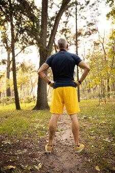 Uomo brizzolato sportivo che si gode la giornata di sole nella foresta