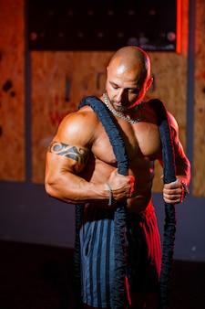 Uomo forte bello sportivo in posa con la corda sportiva sullo sfondo della palestra. un bodybuilder forte con addominali, spalle, bicipiti, tricipiti e petto perfetti.