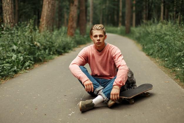 Giovane bello sportivo con skateboard e zaino che si siede sull'asfalto