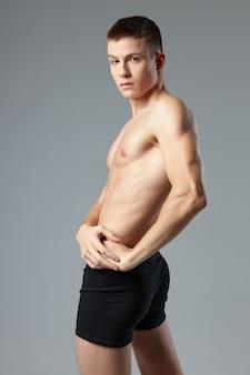 Mutandine nere atleta maschio sportivo in posa allenamento corpo muscoloso.