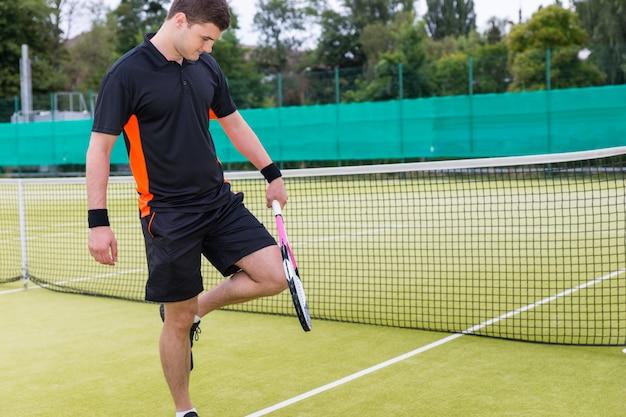 Giocatore di tennis maschile sportivo che indossa un abbigliamento sportivo in fase di riscaldamento prima della partita di tennis su un campo all'aperto in estate o in primavera