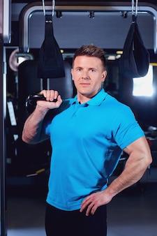 Un maschio sportivo con pesi di manubri in mano la palestra